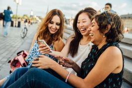 Three diverse friends enjoying a funny cell phone video.