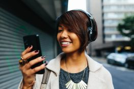 Young Businesswoman listening music on the Street with Headphones.