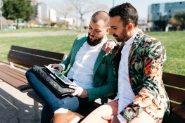 Portrait of bearded men in bright jackets browsing tablet on bench in sunny park.