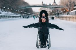 Man in wheelchair and woman skating on canal.
