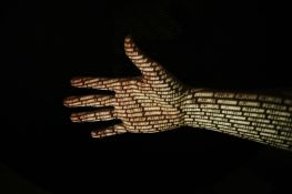 Hand In Front Of Black Background With Binary Code Projected Onto The Skin.